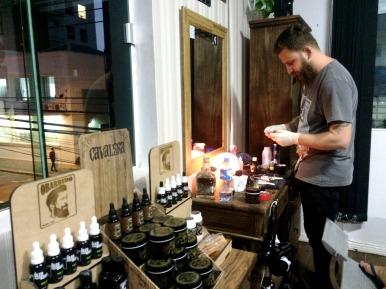 Na foto, produtos específicos para uso em barbas e Dimas preparando as navalhas para atender um cliente